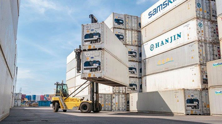 Top-loading container handler at a dock removing two very large shipping containers from a stack of containers.